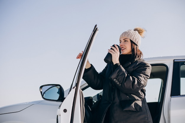 車に座ってコーヒーを飲む女性 無料写真