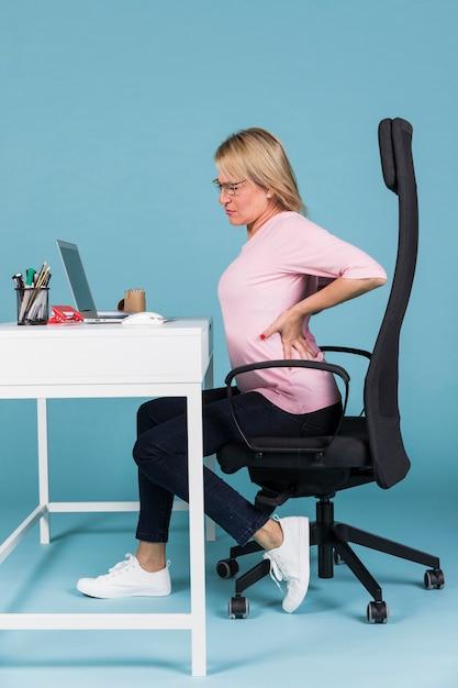Женщина сидит в кресле страдает от боли в спине во время работы на ноутбуке Premium Фотографии