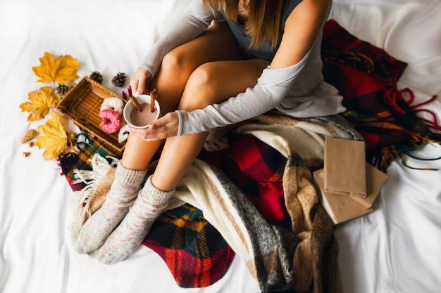 本と彼女のベッドに座って、シナモン、クッキー、艶をかけられたドーナツとコーヒーを飲む女性。 無料写真