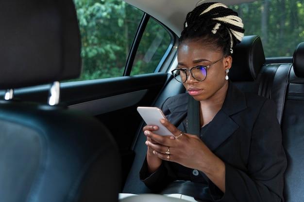 Donna seduta all'interno della sua auto e guardando smartphone Foto Gratuite