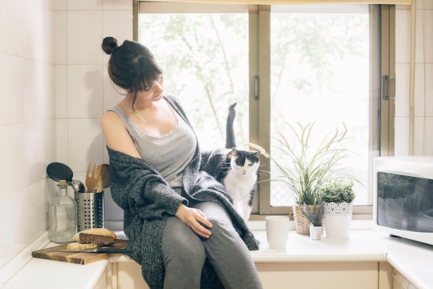 Free Photo | Woman sitting in kitchen with her cat