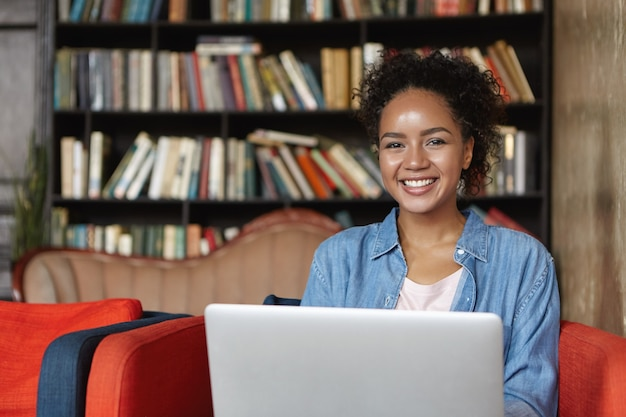 Woman sitting in a library with her laptop Free Photo