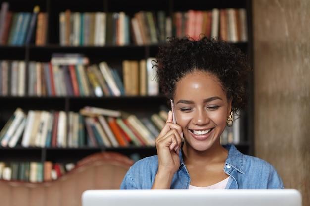 Donna seduta in una libreria con il suo laptop Foto Gratuite