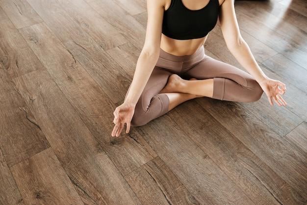 Woman sitting in lotus pose and meditating at yoga studio Premium Photo