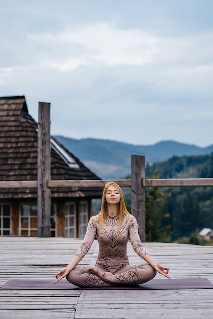 A woman sitting in lotus position at the morning on a fresh air. Free Photo