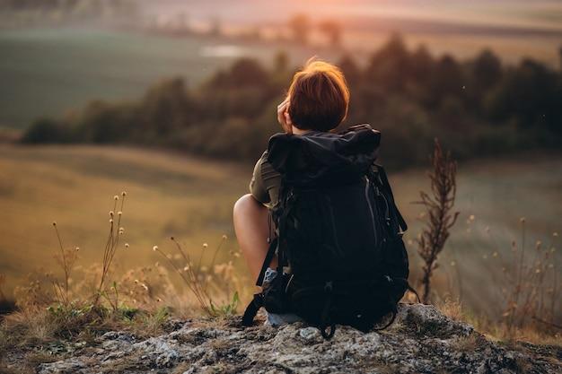 Woman sitting on the mountain Free Photo
