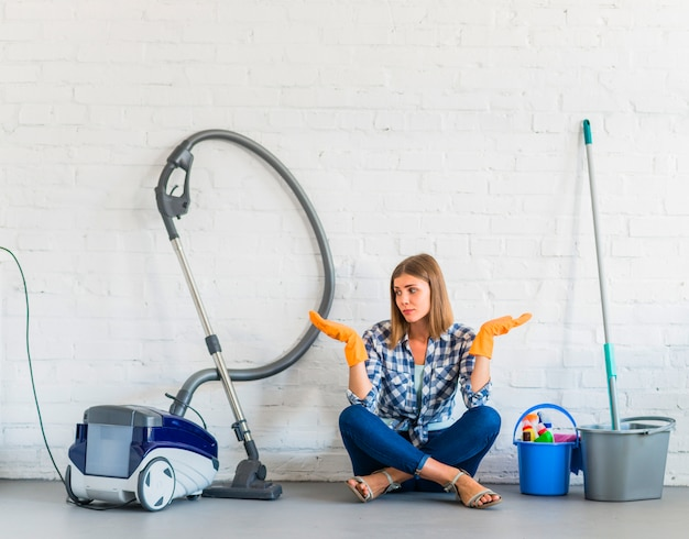 Woman sitting near cleaning equipments shrugging Free Photo