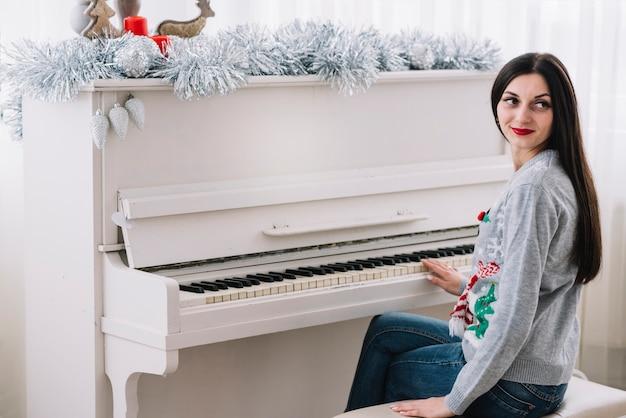 Woman sitting near piano Free Photo