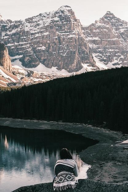 モレーン湖の近くに座って、雪に覆われた山を眺めている女性 無料写真
