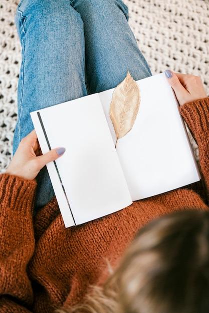開いたノートブックに金色のぱりっとした葉とニットの敷物の上に座っている女性 無料写真