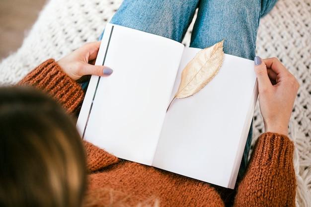 Женщина сидит на вязаном коврике с золотым хрустящим листом на открытом блокноте Бесплатные Фотографии