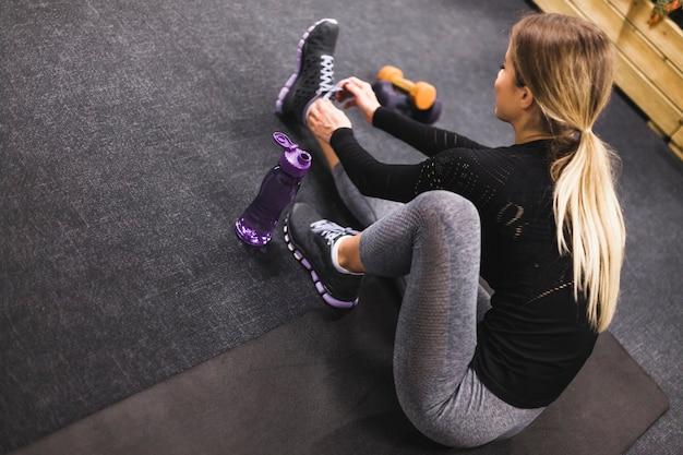 Женщина, сидя на тренировочный мат, связывая шнурки Бесплатные Фотографии