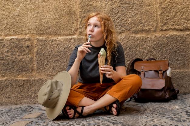 Женщина сидит на земле и ест рожок мороженого Бесплатные Фотографии
