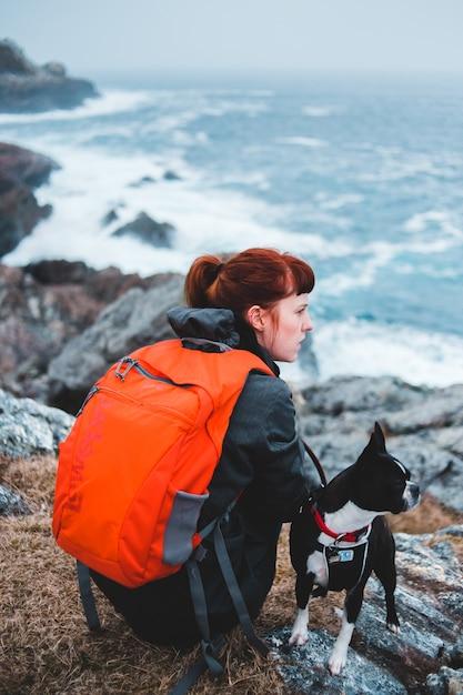 Женщина сидит на возвышенности рядом с собакой Бесплатные Фотографии