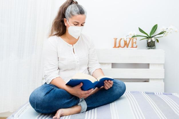 Женщина сидит на диване у себя дома с книгой с антивирусной маской Premium Фотографии