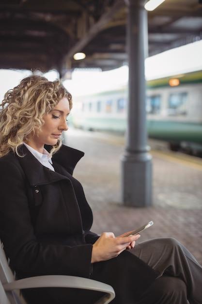 휴대 전화를 사용 하여 플랫폼에 앉아 여자 무료 사진