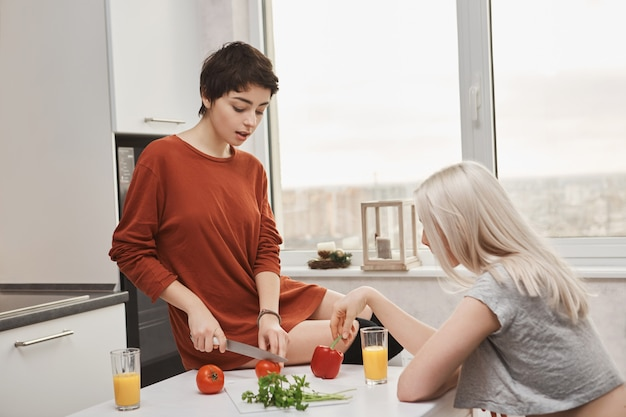 Женщина сидит на столе, резает томото, пока ее подруга пьет апельсиновый сок Бесплатные Фотографии