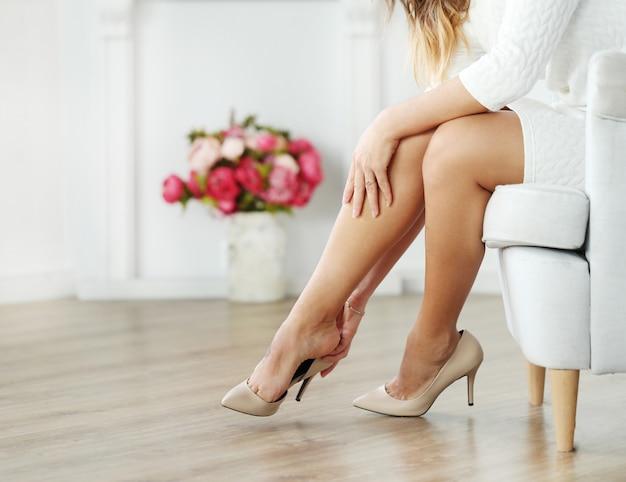 Женщина сидит на кресле и носит бежевые каблуки Бесплатные Фотографии