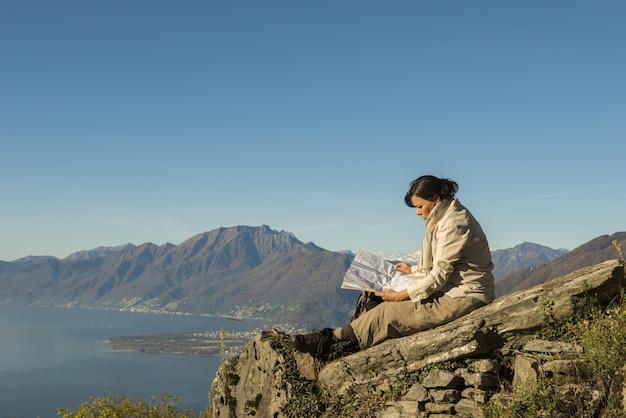 海岸近くの山の美しい景色を望む岩の上に座っている女性 無料写真