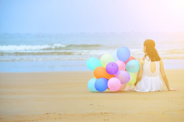 Woman sitting on the sand next to a bunch of balloons Free Photo