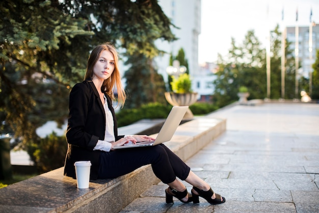 Woman sitting outdoors with laptop Free Photo