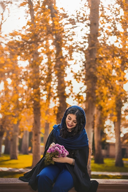Woman sitting in the park and holding a bouquet of flowers Free Photo