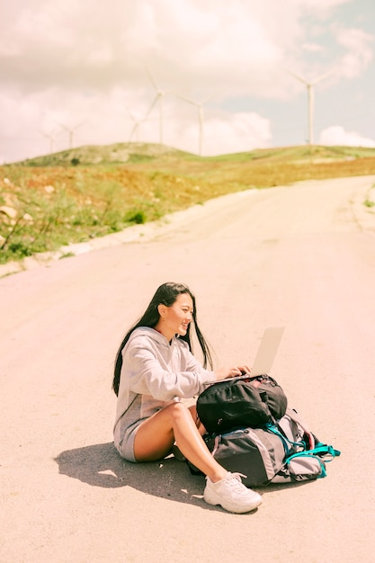 Woman sitting on road and working on laptop placed on backpacks Free Photo