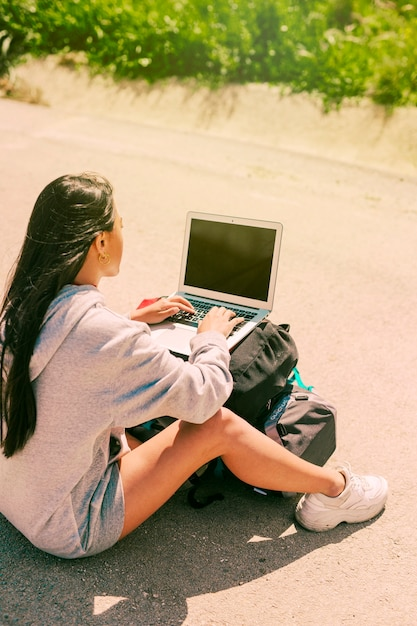 Woman sitting on road and working on notebook placed on backpacks Free Photo