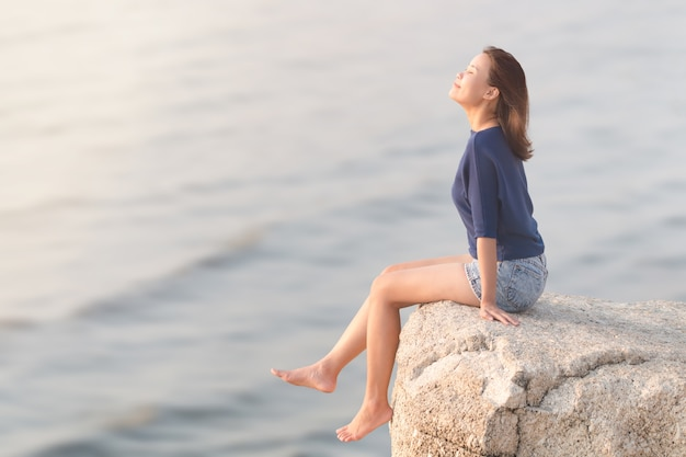 Woman sitting on the rock cliff and breathing fresh air. Premium Photo