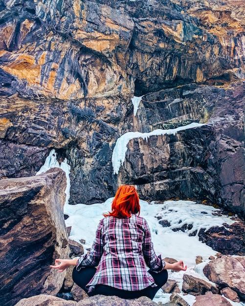 The woman sitting on the rock mountain. young yoga woman sit meditation on mountain peak rock. Premium Photo