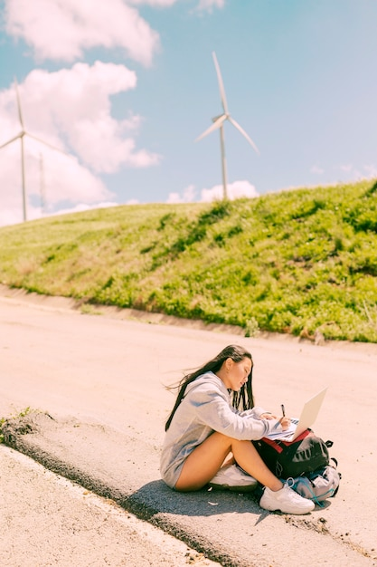 Woman sitting on side of road and working on laptop placed on backpacks Free Photo
