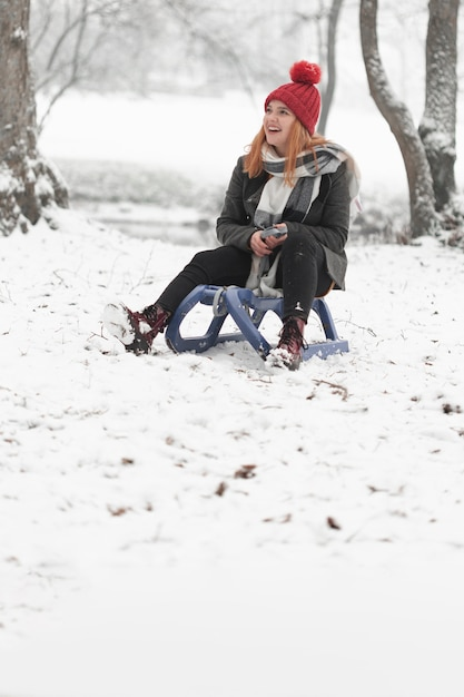 Woman sitting on a sleigh outdoors Free Photo