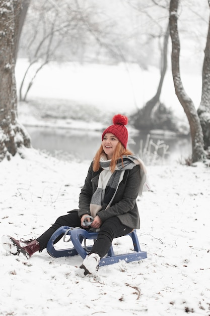 Woman sitting on a sleigh in winter daylight Free Photo