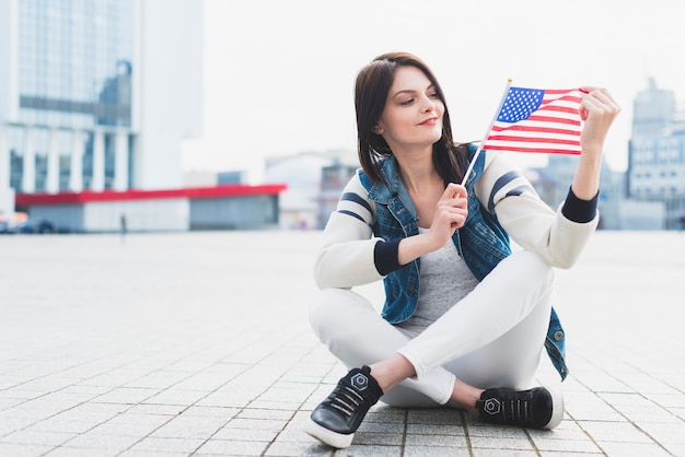 Woman sitting on square and holding american flag in hand Free Photo