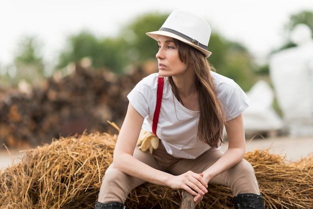 Woman sitting on straw in a farm Free Photo