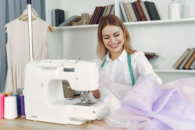 Woman sitting in studio and sew cloth Free Photo