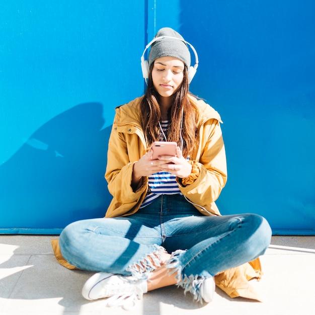 Woman sitting in sunlight in front of door using cellphone wearing headphones Free Photo