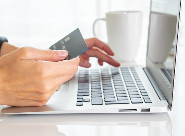 Woman sitting at table, drinking tea and looking at laptop, pay for purchases Premium Photo