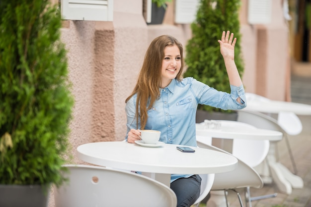 Woman sitting at urban cafe in summer and asking for waiter. Premium Photo