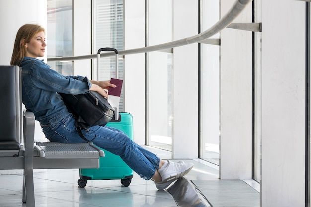 Женщина сидит во время ожидания самолета Premium Фотографии