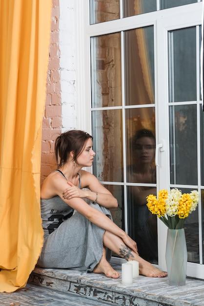 Woman sitting on window sill Premium Photo