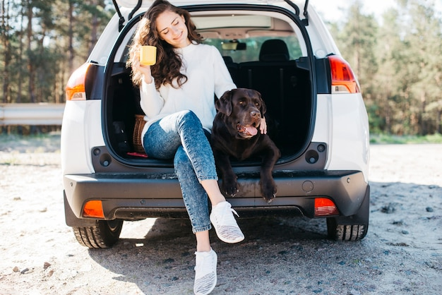 Woman sitting with her dog in open trunk Free Photo