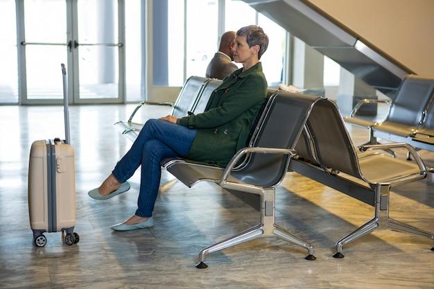 Женщина, сидящая с багажом в зоне ожидания Бесплатные Фотографии
