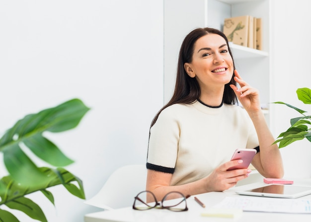Woman sitting with smartphone at table in office Free Photo