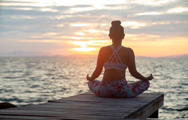 Woman Sitting In Yoga Meditating Pose At Sea Side Against Beautiful