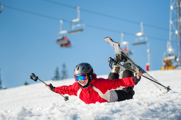 Woman in ski goggles lying with raised arms on snowy slope Premium Photo