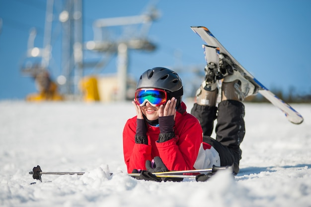 Woman skier lying with skis on snowy at mountain top Premium Photo