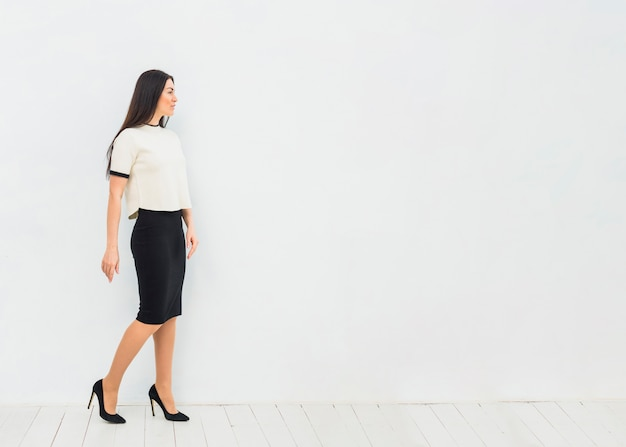 Woman in skirt suit standing on white wall background Free Photo