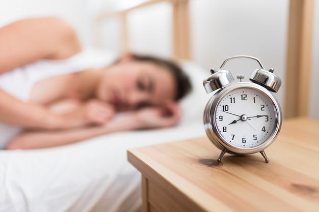 Woman sleeping on bed near alarm clock on wooden desk Free Photo