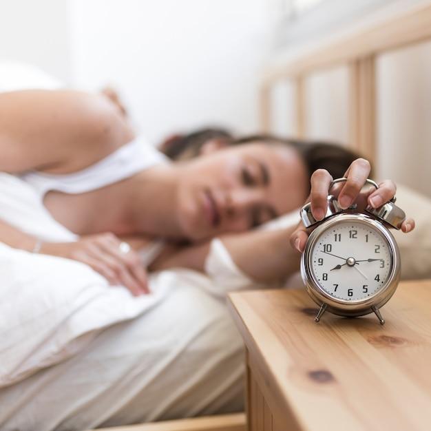 Woman sleeping on bed turning off alarm clock Free Photo